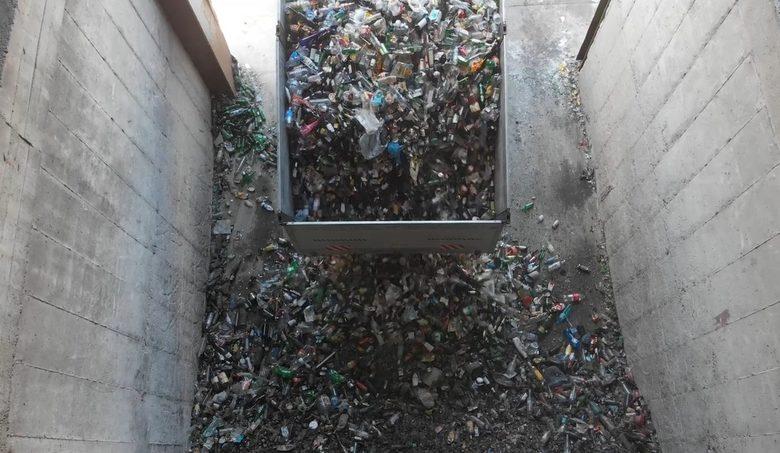 Измерените вече камиони изсипват стъклените отпадъци в приемна зона.